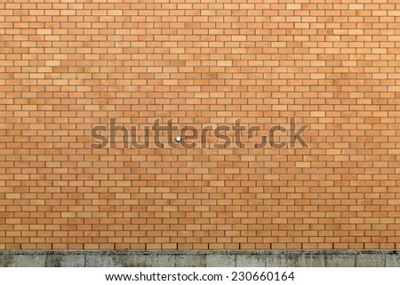 Somewhat clean exterior brick wall with a rather dirty concrete foundation. - stock photo