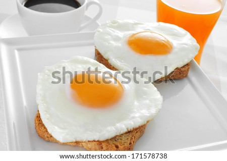 somme heart-shaped fried eggs served on bread, a cup of coffee and a glass of orange juice on a set table - stock photo