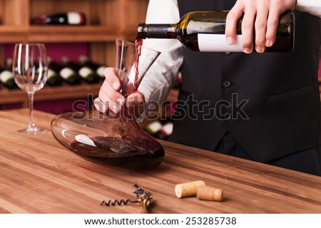 Sommelier at work. Confident male sommelier pouring wine to decanter while standing near the wine shelf  - stock photo