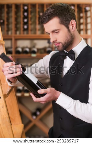 Sommelier choosing wine. Confident young man in waistcoat and bow tie holding bottle with wine and looking at it while standing in liquor store