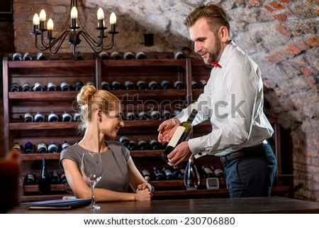 Sommelier helping young woman to choose wine in the cellar. Wine degustation - stock photo