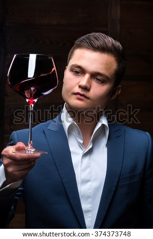 Sommelier in suite looking at red wine. Caucasian businessman looking at the Glass of Red Wine. Confident oligarch looks at a glass of a red wine - stock photo