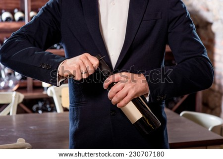 Sommelier opening wine bottle in the wine cellar - stock photo