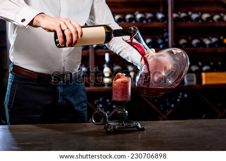 Sommelier pouring wine to the decanter in the wine cellar - stock photo