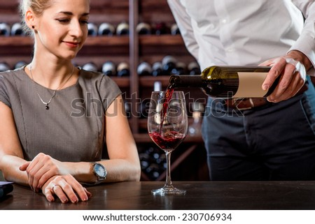 Sommelier pouring wine to the glass with woman in the cellar. Wine degustation