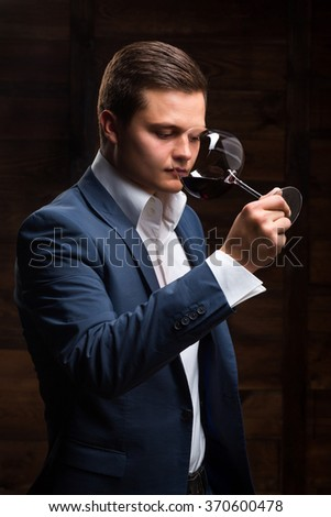 Sommelier tasting red wine. Caucasian Man Tasting a Glass of Red Wine. Satisfied mature sommelier smell at a glass of a red wine - stock photo
