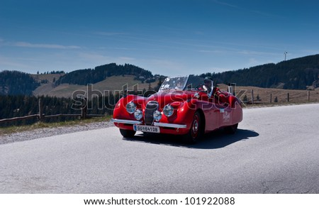 "SOMMERALM, AUSTRIA - APRIL 27:Erich Hofer in a 1952 Jaguar XK 120 OTS participates in a rally for vintage cars ""Suedsteiermark Classic"" on April 27, 2012 in Sommeralm, Austria."