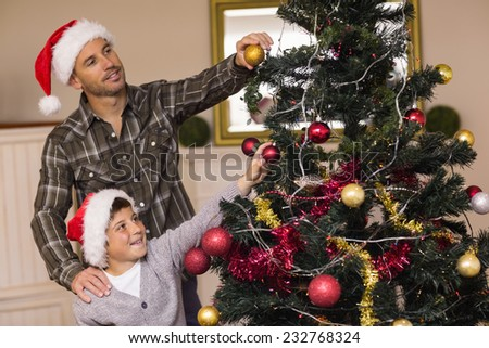 Son and dad decorating the christmas tree at home in the living room - stock photo