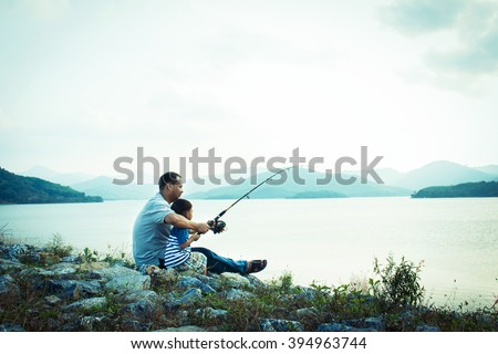 son and dad fishing at dam,vintage tone - stock photo