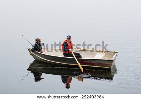 son and dad fishing in a row boat - stock photo