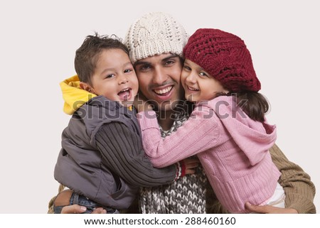 Son and daughter embracing father - stock photo