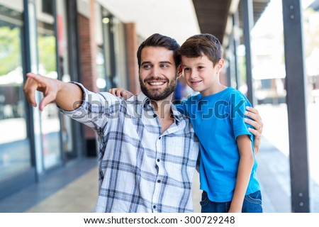 Son and father look away at the mall - stock photo