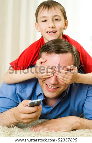 son and father lying on the carpet - stock photo