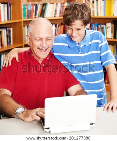 Son and father on the computer at the library.   - stock photo