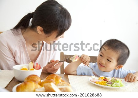 Son and mother having breakfast - stock photo