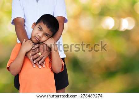 son embrace his father on green bokeh background - stock photo