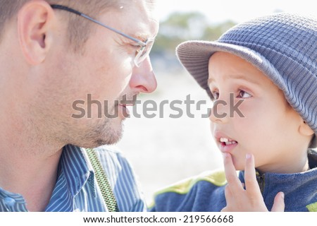 son father look each other talk closeup outdoor - stock photo