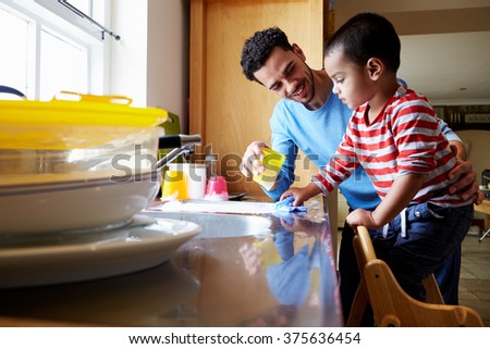 Son Helping Father To Wash Dishes In Kitchen Sink - stock photo