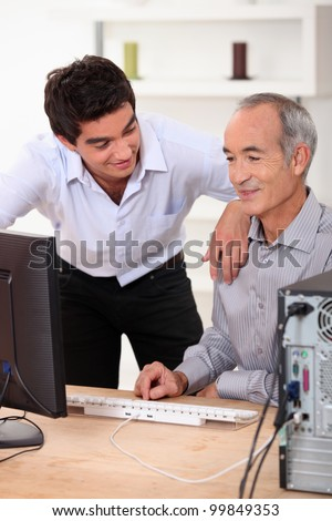 Son helping father with computer