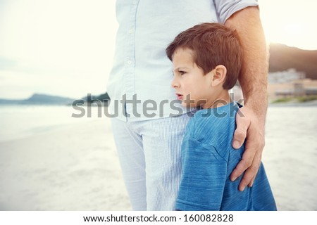 Son hugging fathers leg at beach feeling safe and love - stock photo