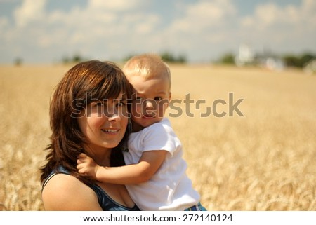 son in his mothers arms on the field - stock photo