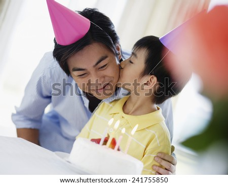 Son Kissing Father's Cheek at Birthday Party - stock photo