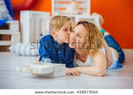 Son kissing happy mother - stock photo