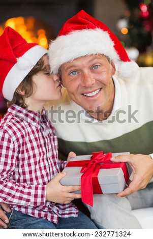 Son kissing his father after receiving a christmas gift at home in the living room - stock photo