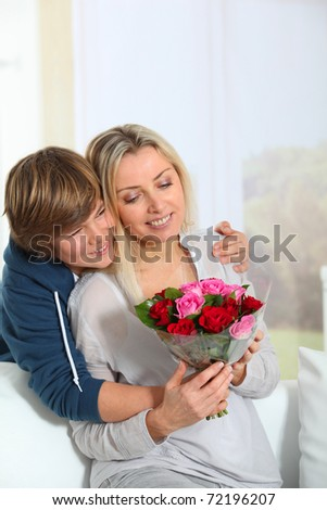 Son offering bunch flowers on mother's birthday - stock photo