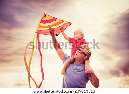 Son on Father's Shoulder at Sunset Flying a Kite Together - stock photo