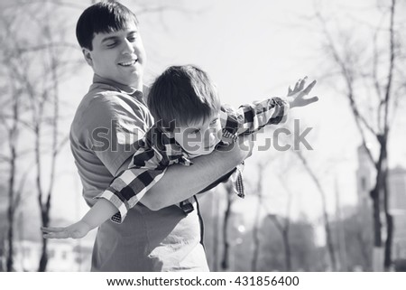 Son on fathers at the park having fun together, black and white image. - stock photo