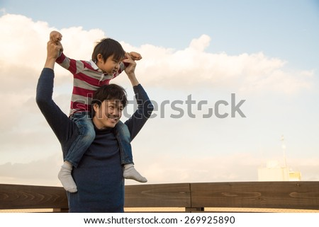 Son on fathers shoulders in Tokyo - stock photo