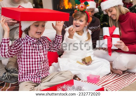 Son playing with a gift sitting on the floor with his family at home in the living room - stock photo
