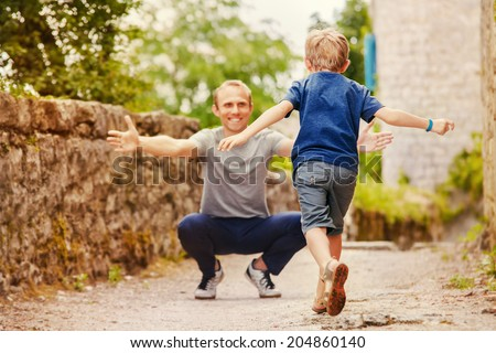 Son runs to daddy's arms - stock photo