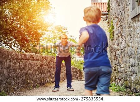 Son runs to his father hugs - stock photo