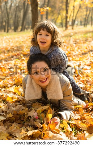 Son sitting on top her mother and having fun together in autumn park - stock photo