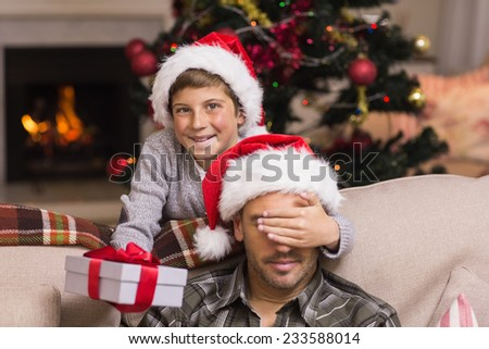 Son surprising his father with christmas gift at home in the living room - stock photo