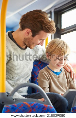 Son Using Digital Tablet On Bus Journey With Father - stock photo