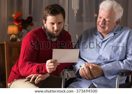 Son visiting ill father in rest home - stock photo