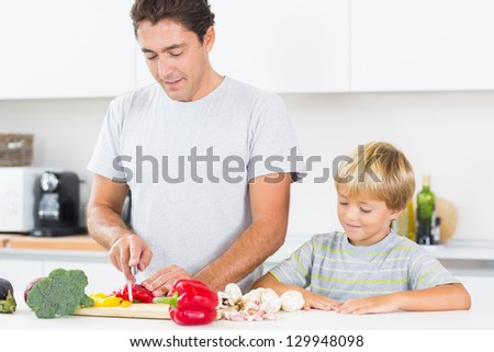 Son watching father preparing vegetables in kitchen