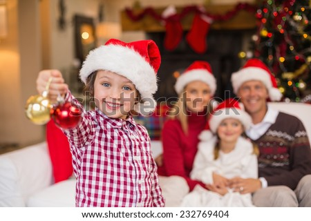 Son wearing santa hat holding baubles in front of his family at home in the living room - stock photo