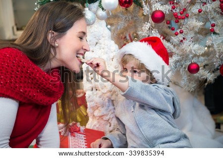 Son wearing Santa's hat and feeding his mother with Christmas cookies at home. - stock photo