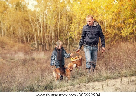 Son with father carry full basket of mushrooms in autumn forest - stock photo