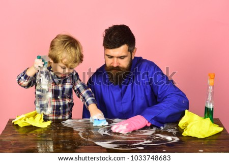 Son with father cleaning together with sponges. Family time concept. Man with cute child on pink background. Guy with beard and mustache in rubber glove and kid holds spray at table.