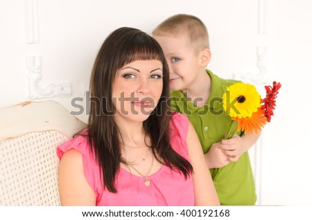 son with flowers hiding behind my mother, my mother smiling happy sitting on the couch - stock photo