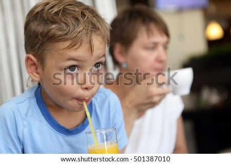 Son with his mother drinking beverages in cafe