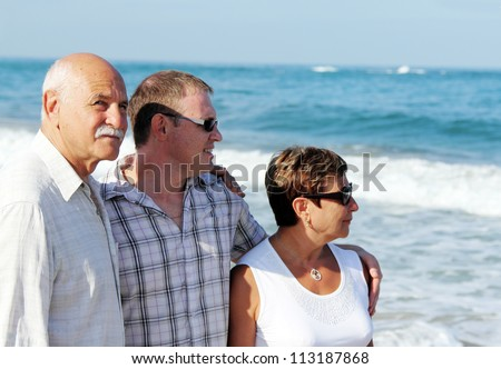 son with his parents on the beach - stock photo