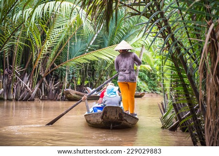 SONG NUOC MIEN TAY, VIETNAM - OCT 5, 2014: Unidentified Vietnamese woman sails a boat with tourists over the Mekong river. Mekong is the 12th longest river in the world