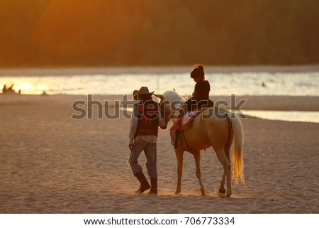 SONGKHLA ,THAILAND- August 31, 2017: Tourist   rides on horse on samilar beach at Songkhla Province, Thailand. August 31, 2017
