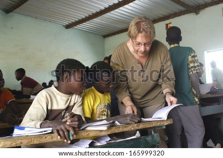 SONGRETENGA - BURKINA FASO - FEBRUARY 26, 2007: Visit of French schoolboy in Africa at the school of Songretenga. A French professor is interested in the African school program. - stock photo